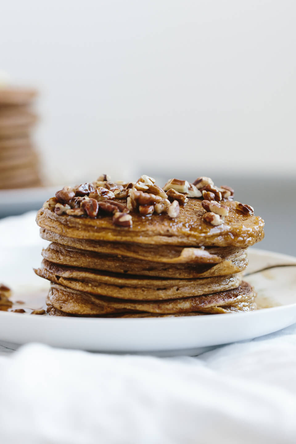 Tall stack of paleo pumpkin pancakes on a plate.
