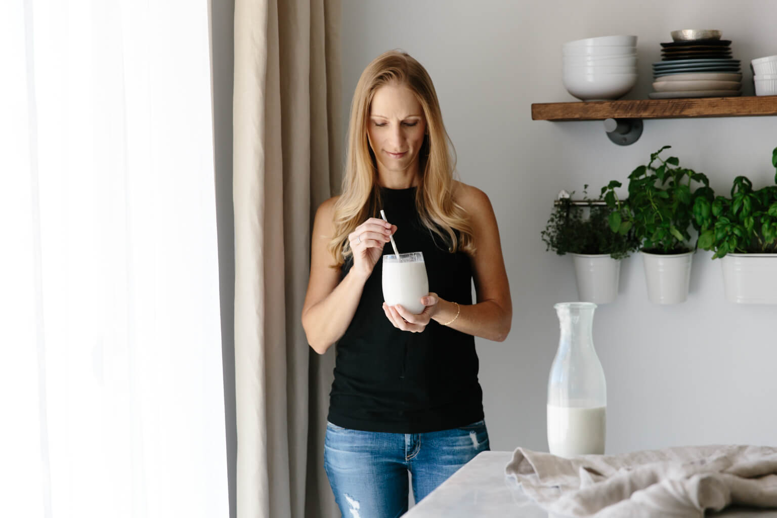 Girl standing and drinking cashew milk