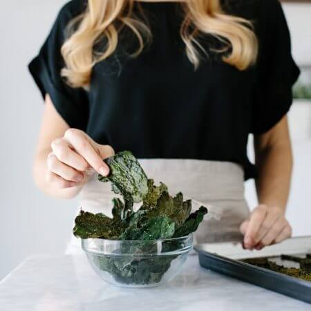 How to make crispy kale chips. A healthy snack that's super easy to make and satisfies all your salty and savory cravings. www.downshiftology.com