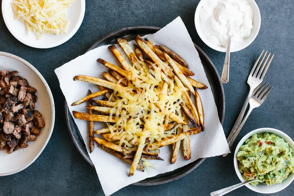 Fries topped with melted cheese and surrounded with bowls of carne asada, guacamole and sour cream.