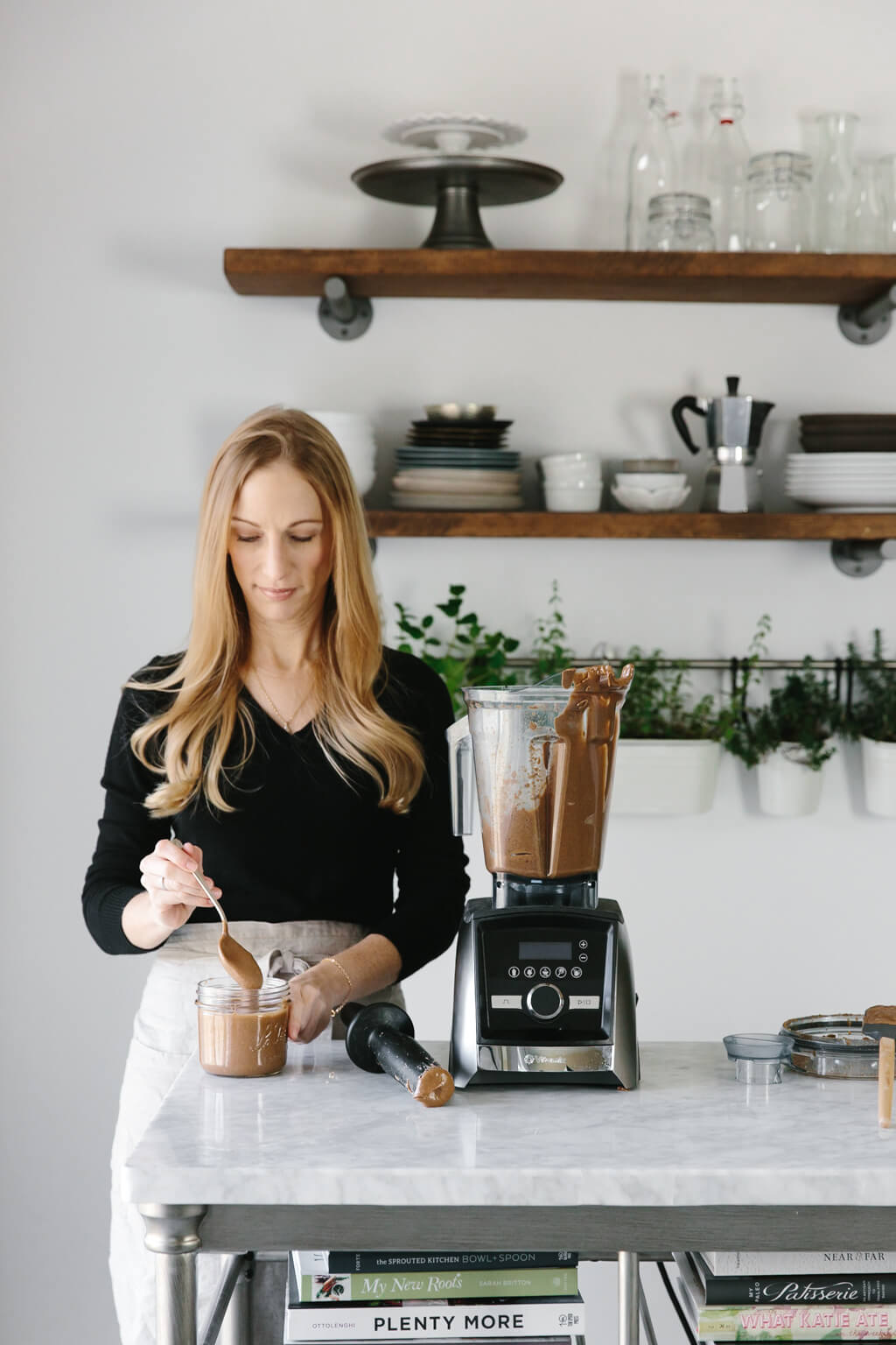 Girl standing next to Vitamix blender with almond butter in it.