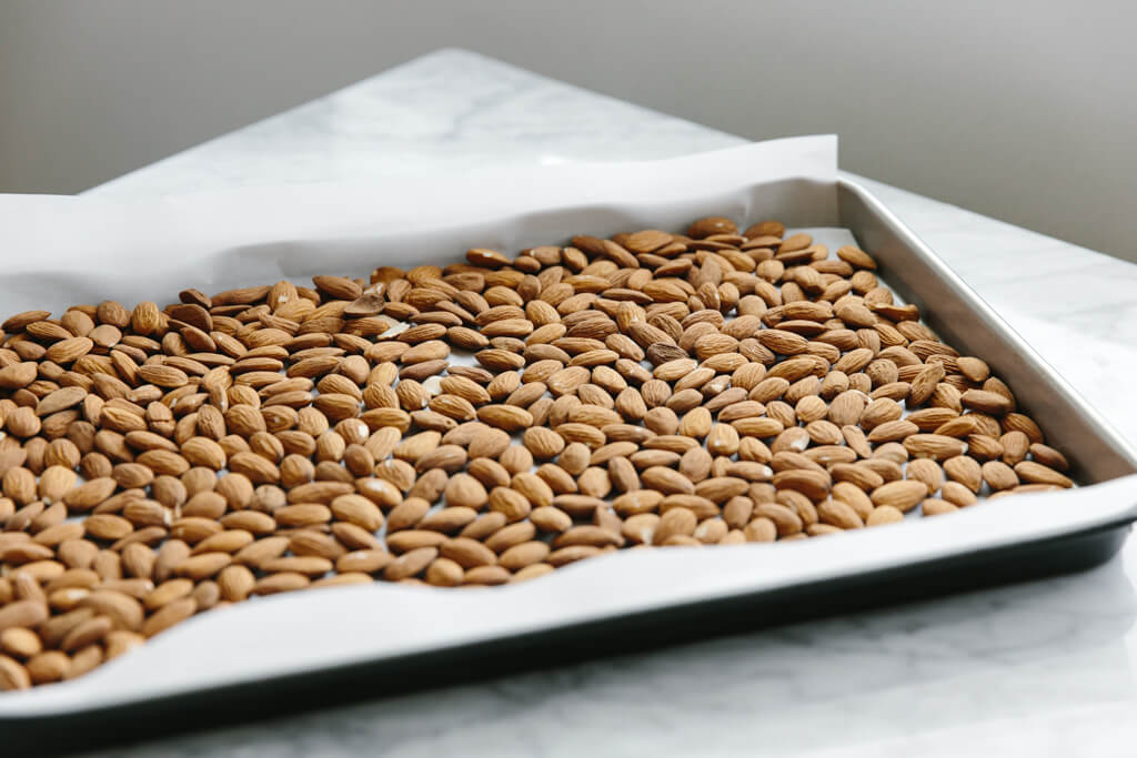 Raw almonds on a baking sheet.