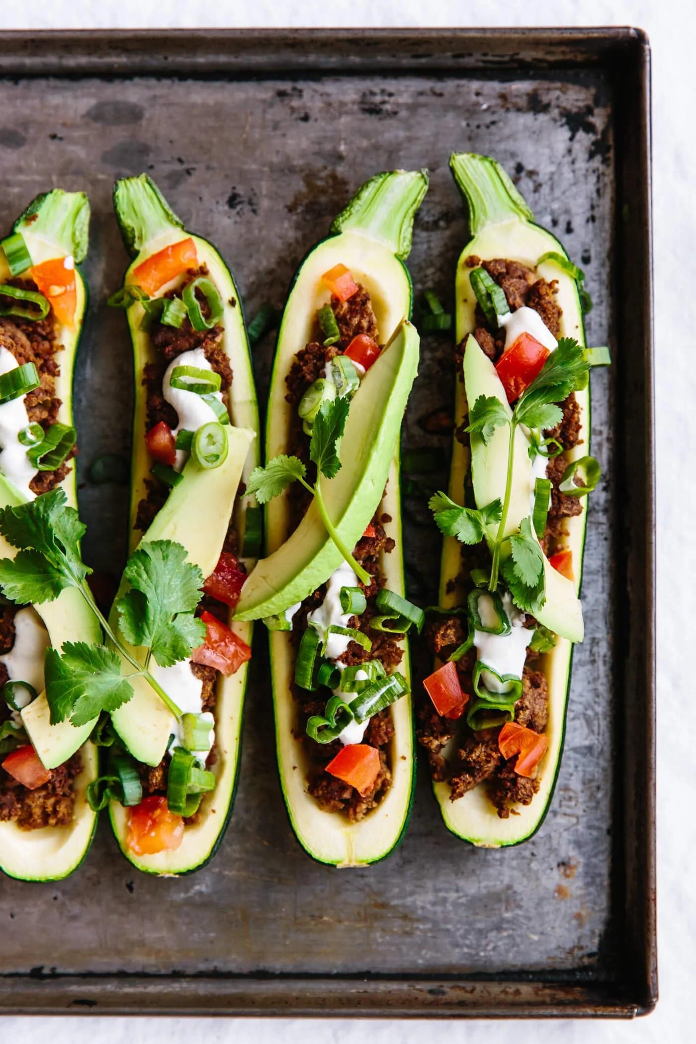 Taco stuffed zucchini boats on a sheet pan.
