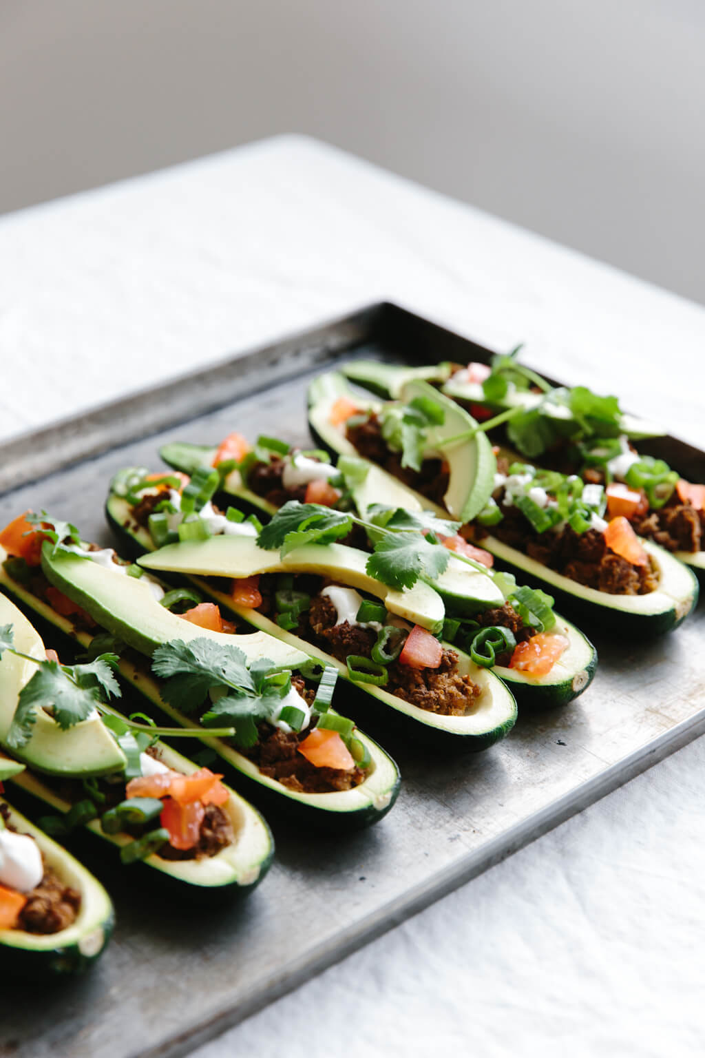 Zucchini boats stuffed with taco filling on a baking tray.