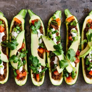 Several taco stuffed zucchini boats on a baking sheet.