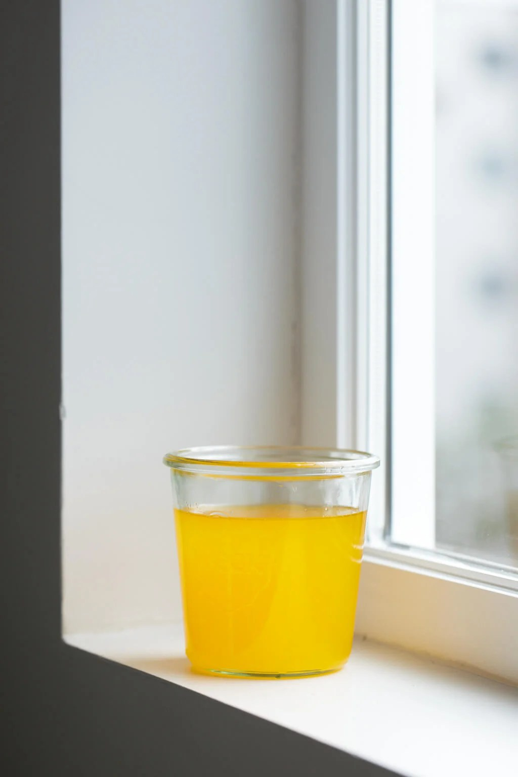 Ghee in a glass jar on a window sill.