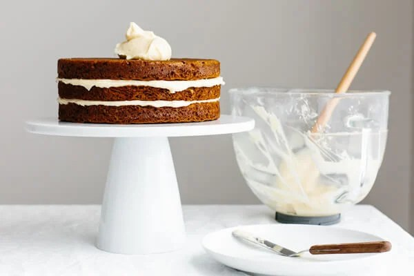 Adding cream cheese frosting to carrot cake.