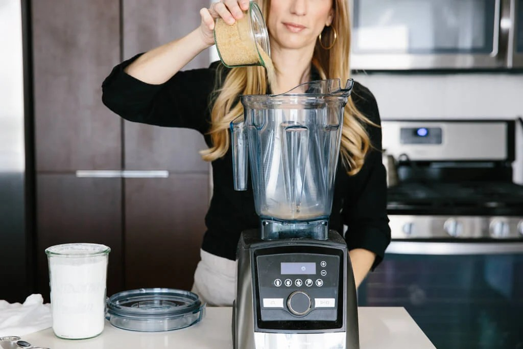 Pouring sugar into a blender.