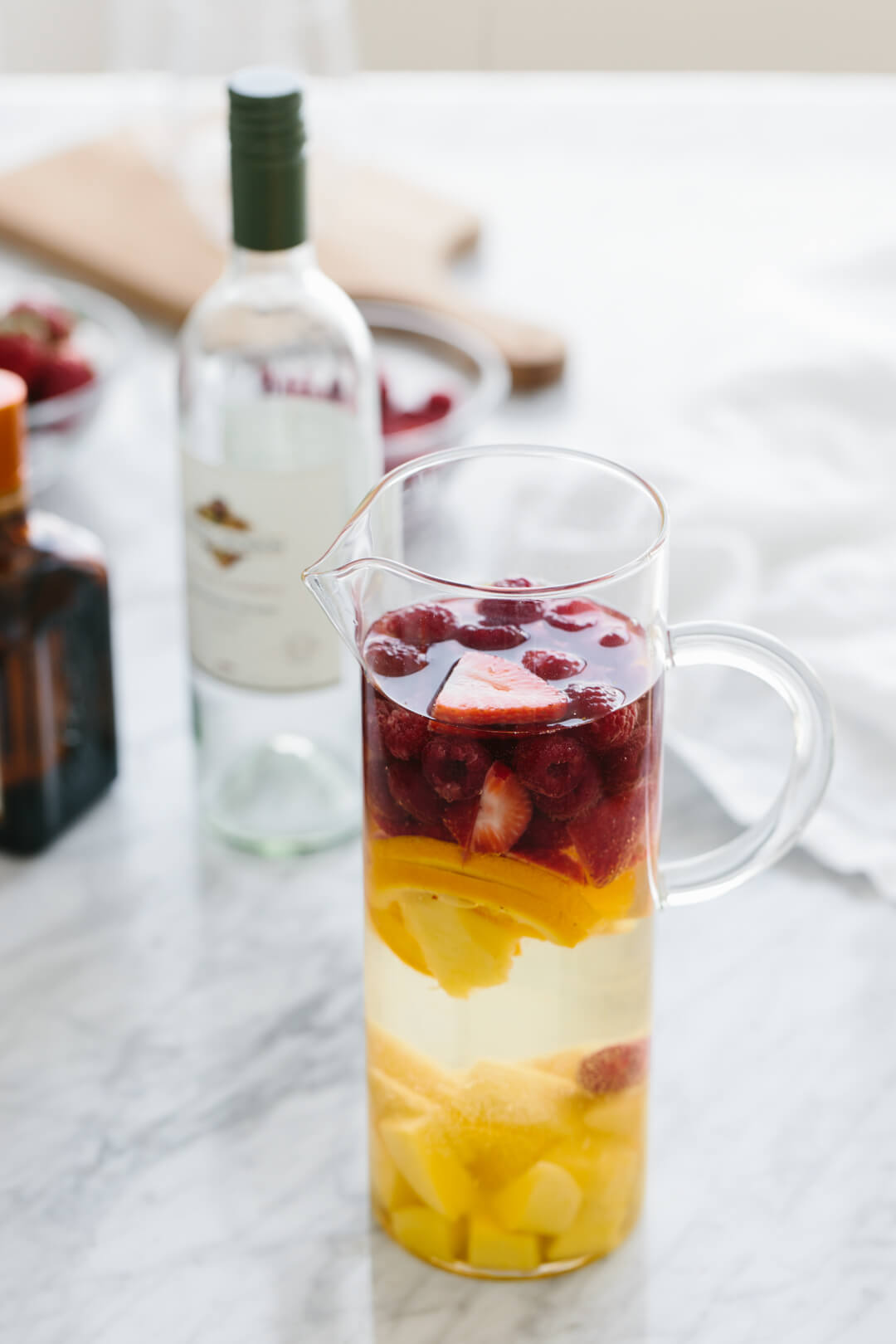 White wine sangria in a pitcher with wine bottle behind it.