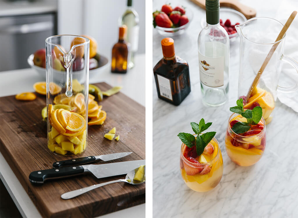 Making white sangria by chopping fruit and adding to a pitcher.