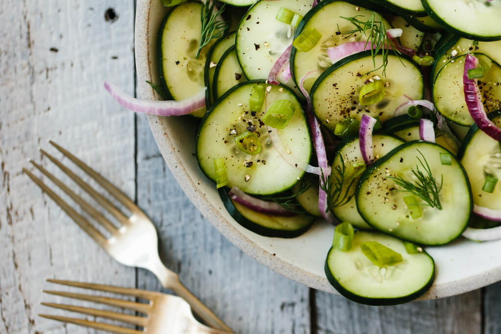 Cucumber salad in a bowl with forks next to it.
