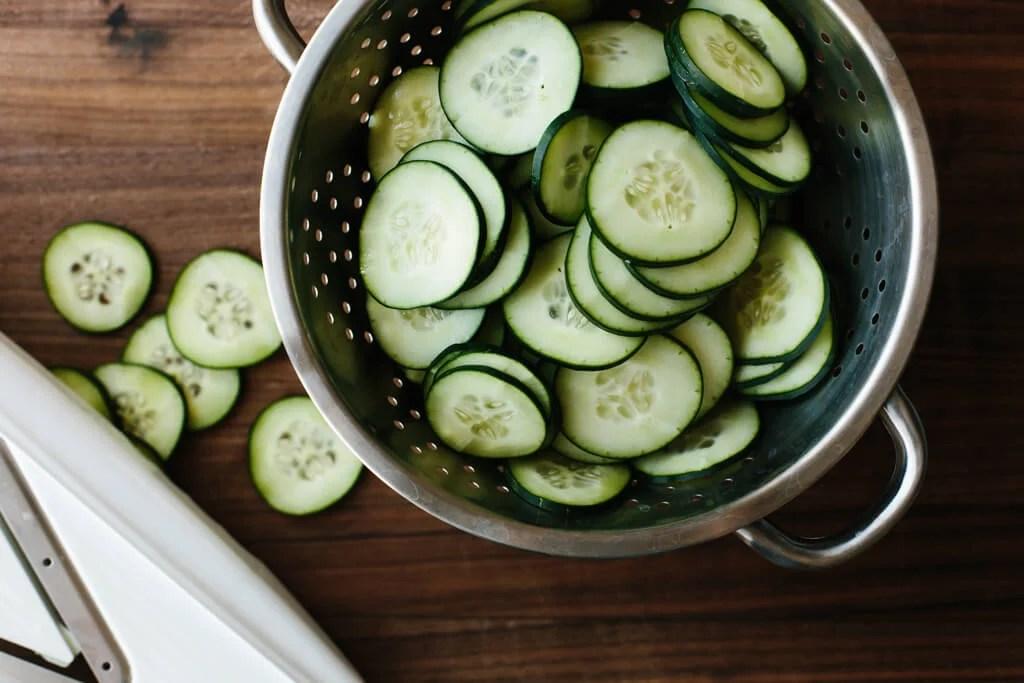 Sliced cucumber in colander.