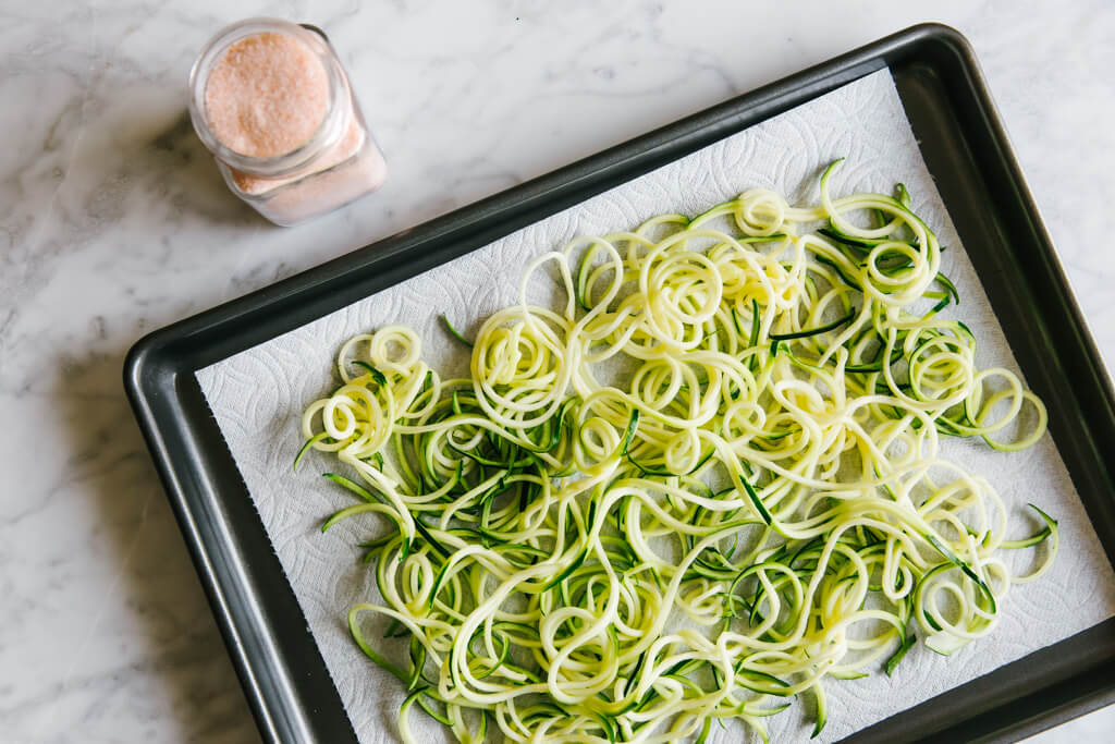 Zucchini noodles on a baking sheet next to a container of salt.