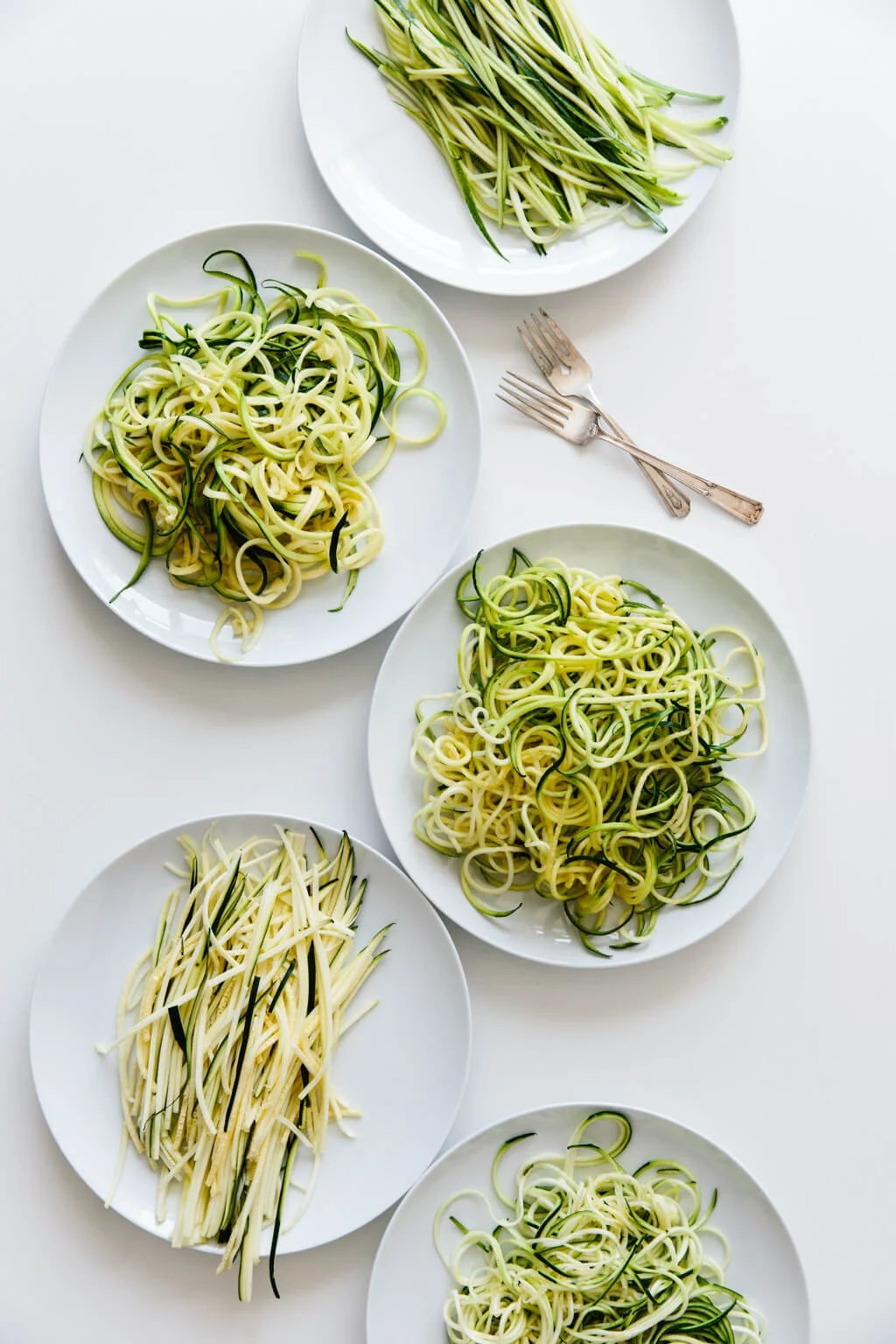 Five plates of zucchini noodles made by different methods.