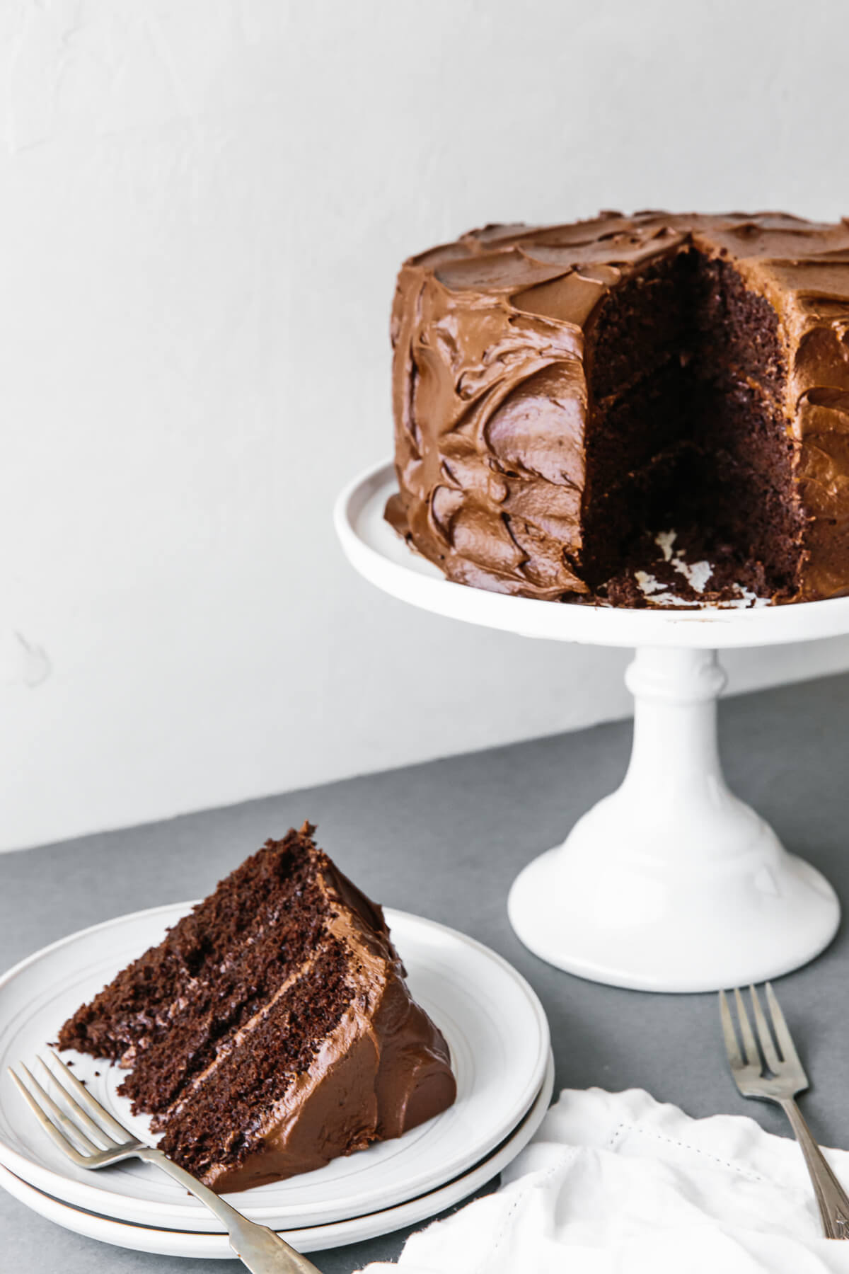Paleo chocolate cake on a cake stand with slice removed to a plate.