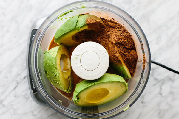 Ingredients for chocolate avocado pudding in a food processor.