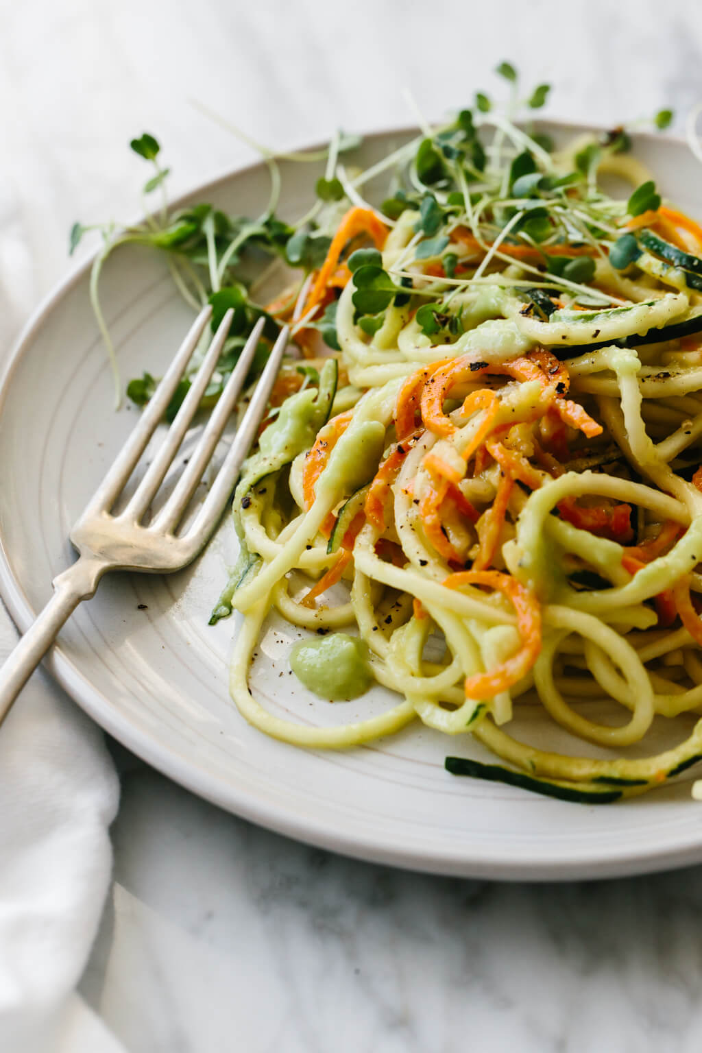 Carrot and zucchini pasta is mixed with a creamy, avocado cucumber sauce for a simple and delicious zucchini noodle recipe that's gluten-free, vegan, paleo and whole30.