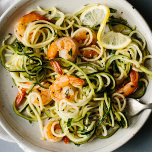 Zucchini noodles on a plate with lemon garlic shrimp.