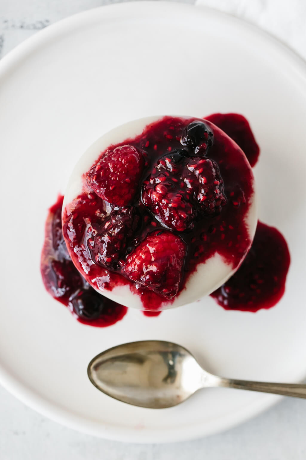 A creamy, dairy-free, coconut panna cotta that's topped with slightly boozy macerated berries. A delicious dessert recipe!
