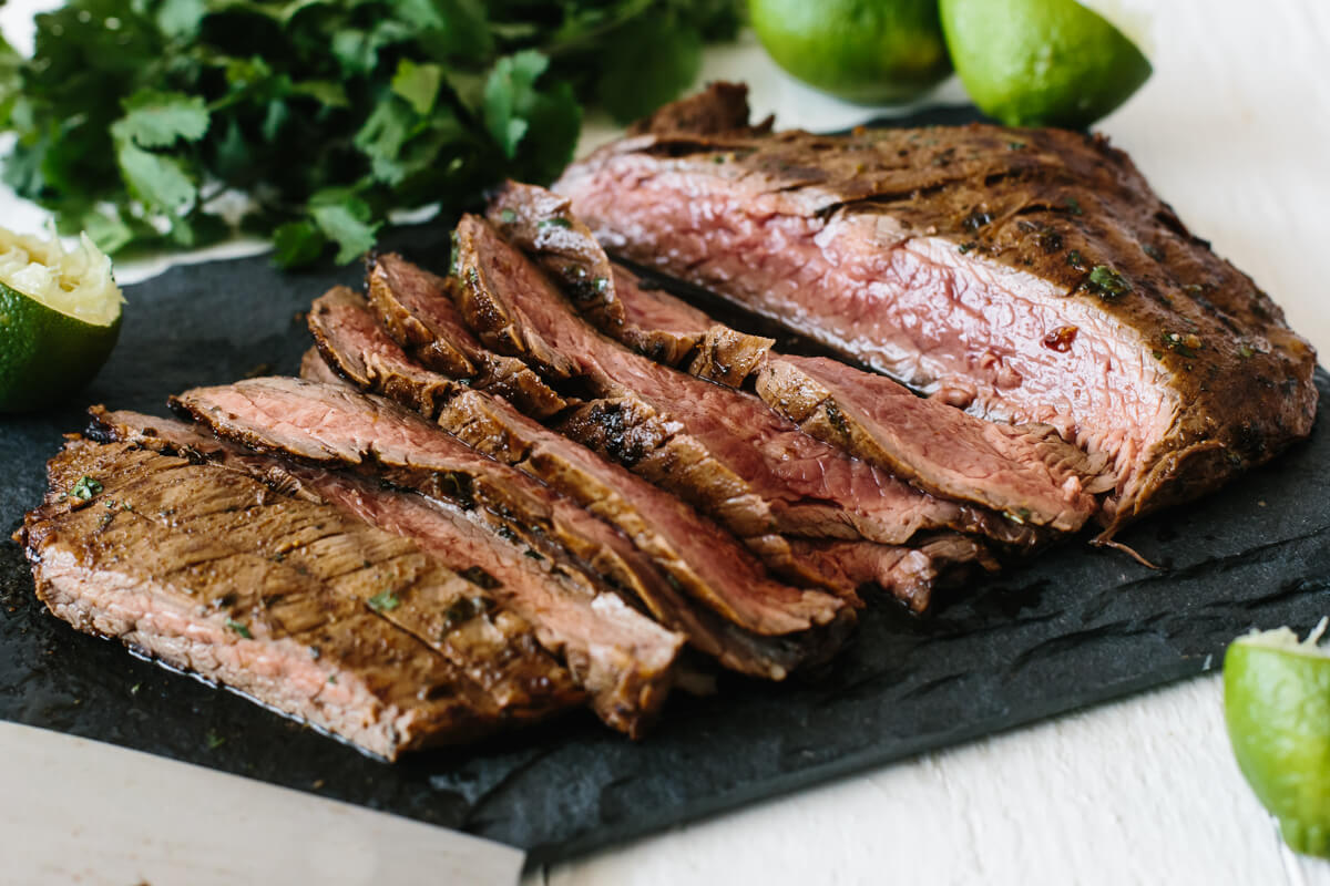 Carne asada sliced on a black platter.