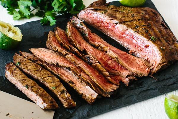 Sliced up grilled carne asada on a board.