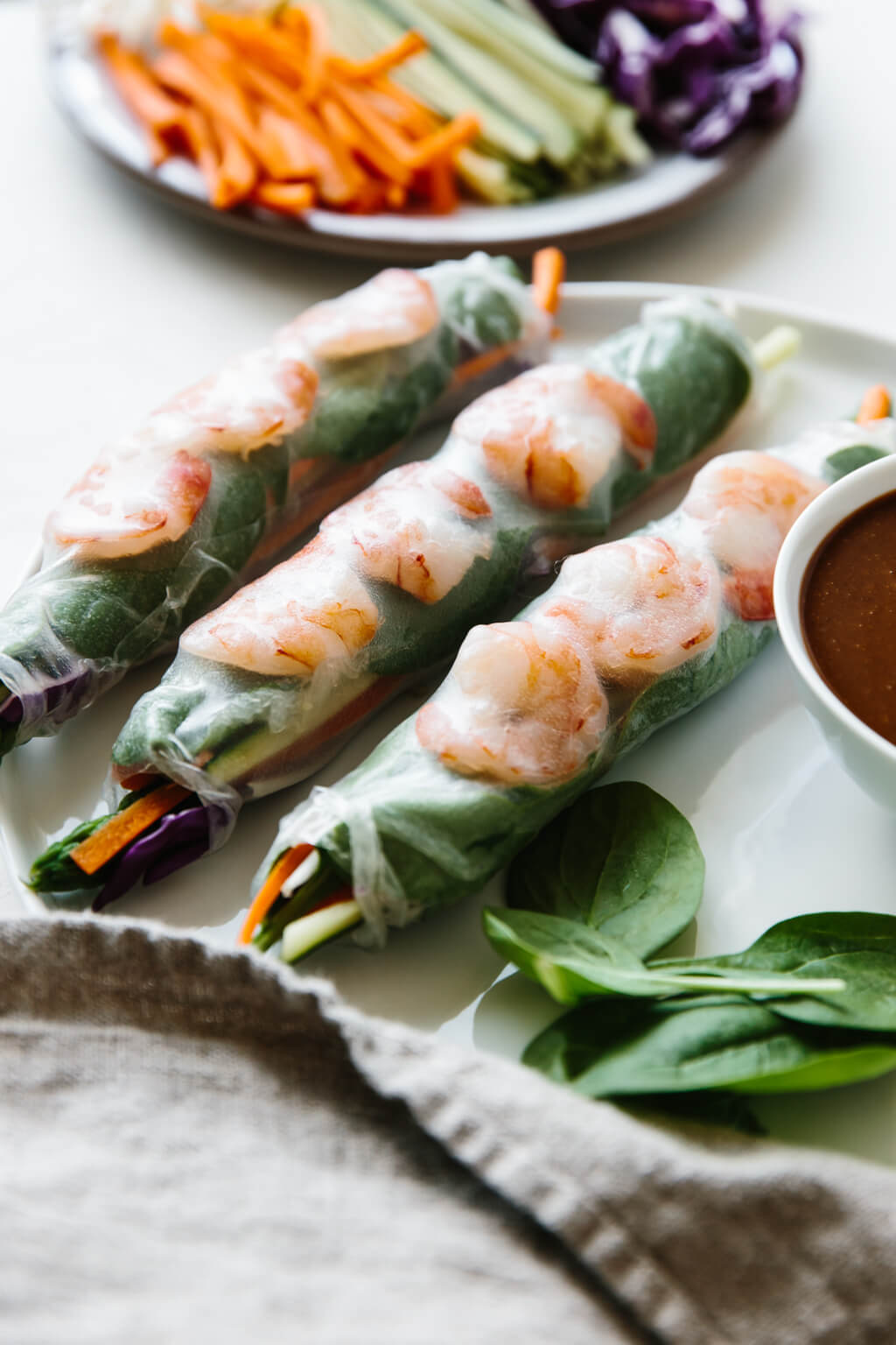 Vietnamese spring rolls on a plate next to dipping sauce.
