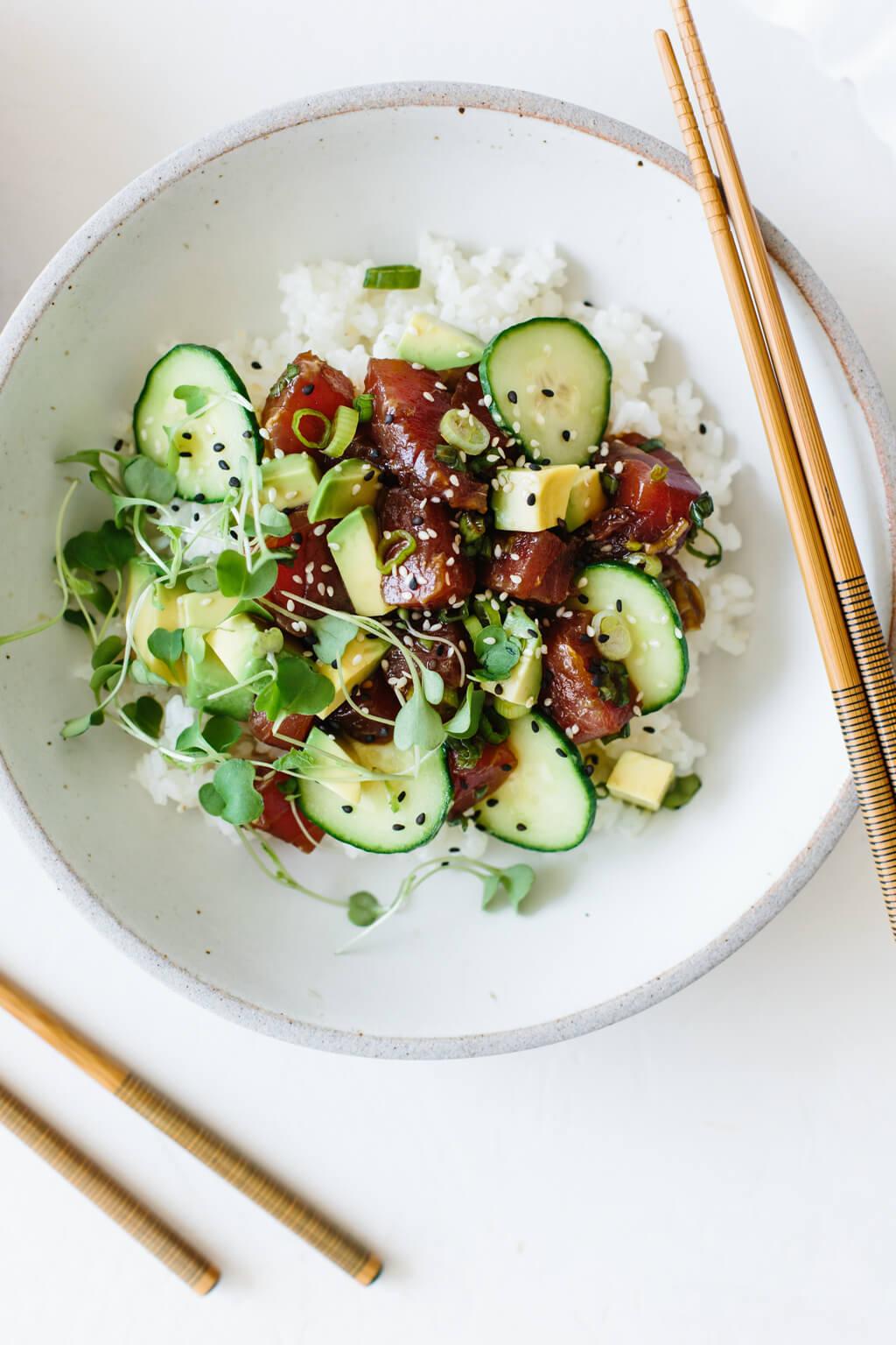 Ahi tuna poke in a white bowl with chopsticks.
