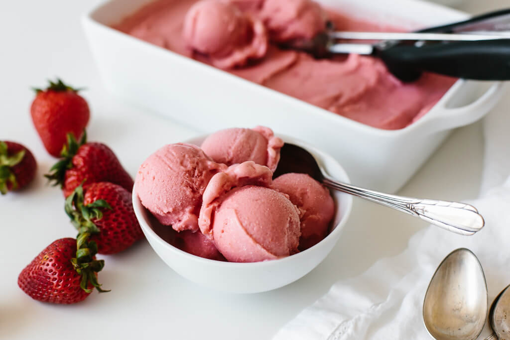 Strawberry frozen yogurt scooped into a white bowl with fresh strawberries next to it.