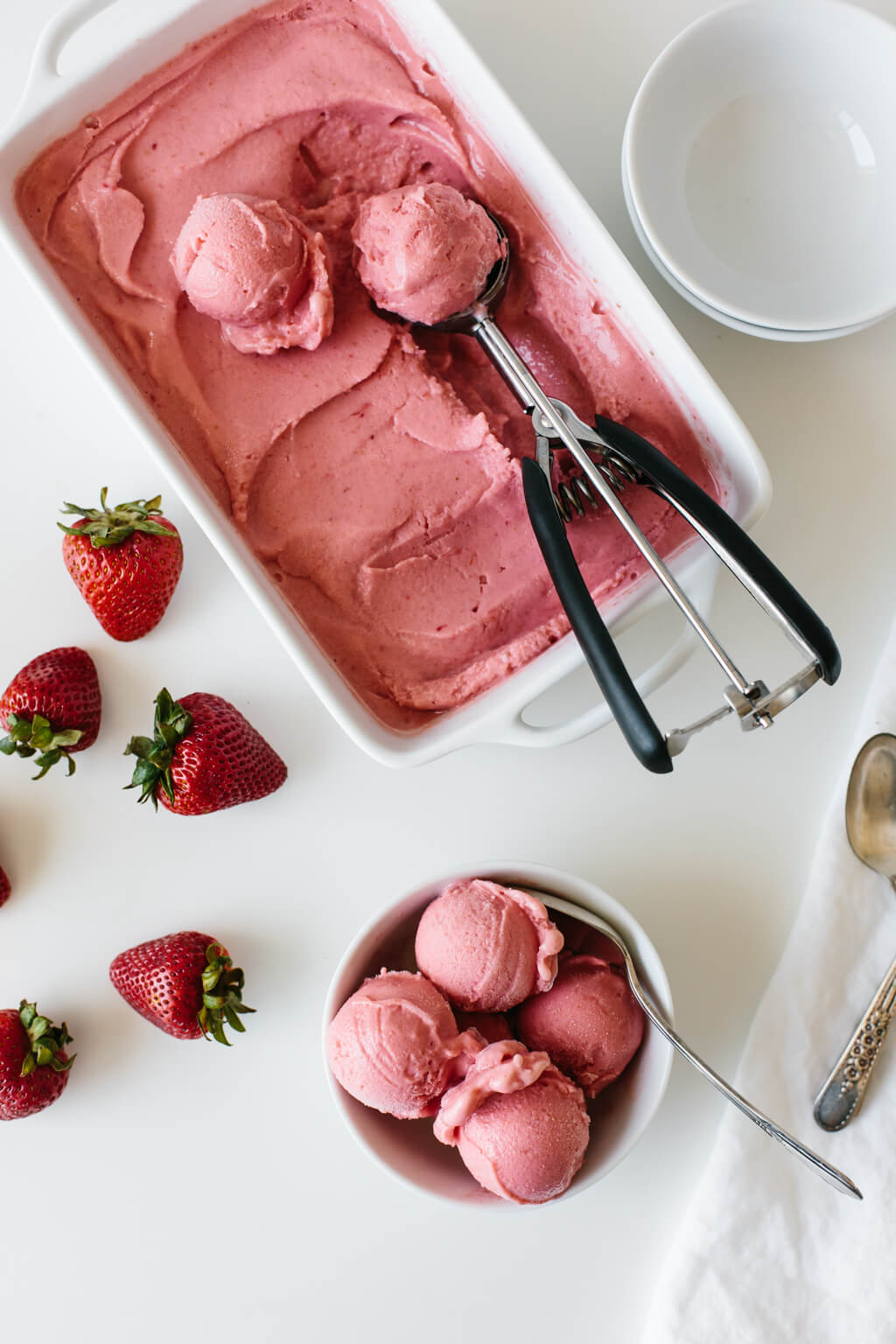 Strawberry frozen yogurt scooped into a bowl.