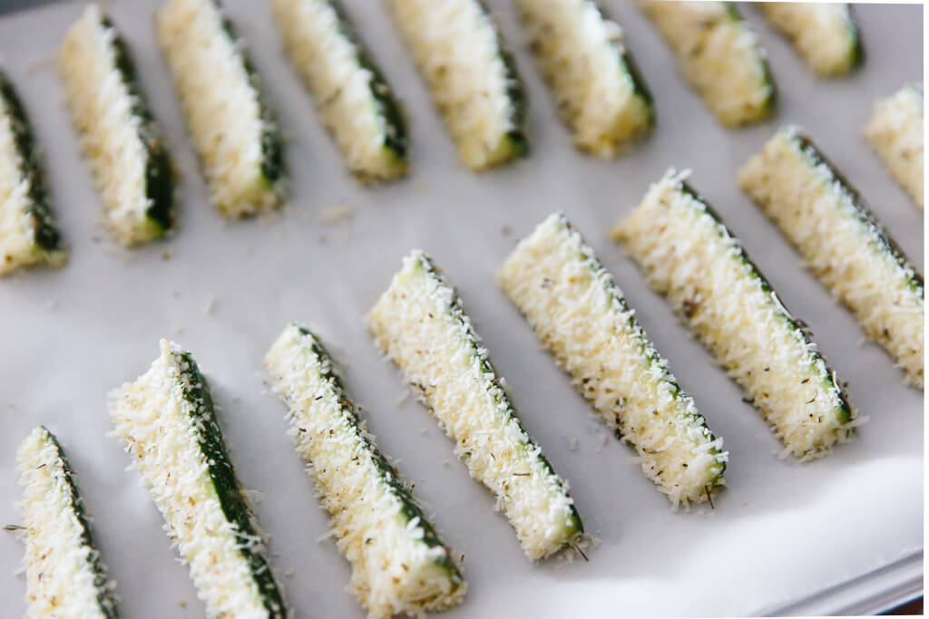 Zucchini fries coated in parmesan and ready to be baked.