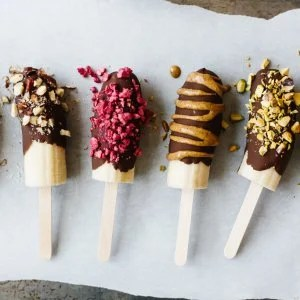 Chocolate covered bananas are frozen bananas dipped in melted chocolate and sprinkled with a variety of toppings including nuts, dried fruit and shredded coconut.