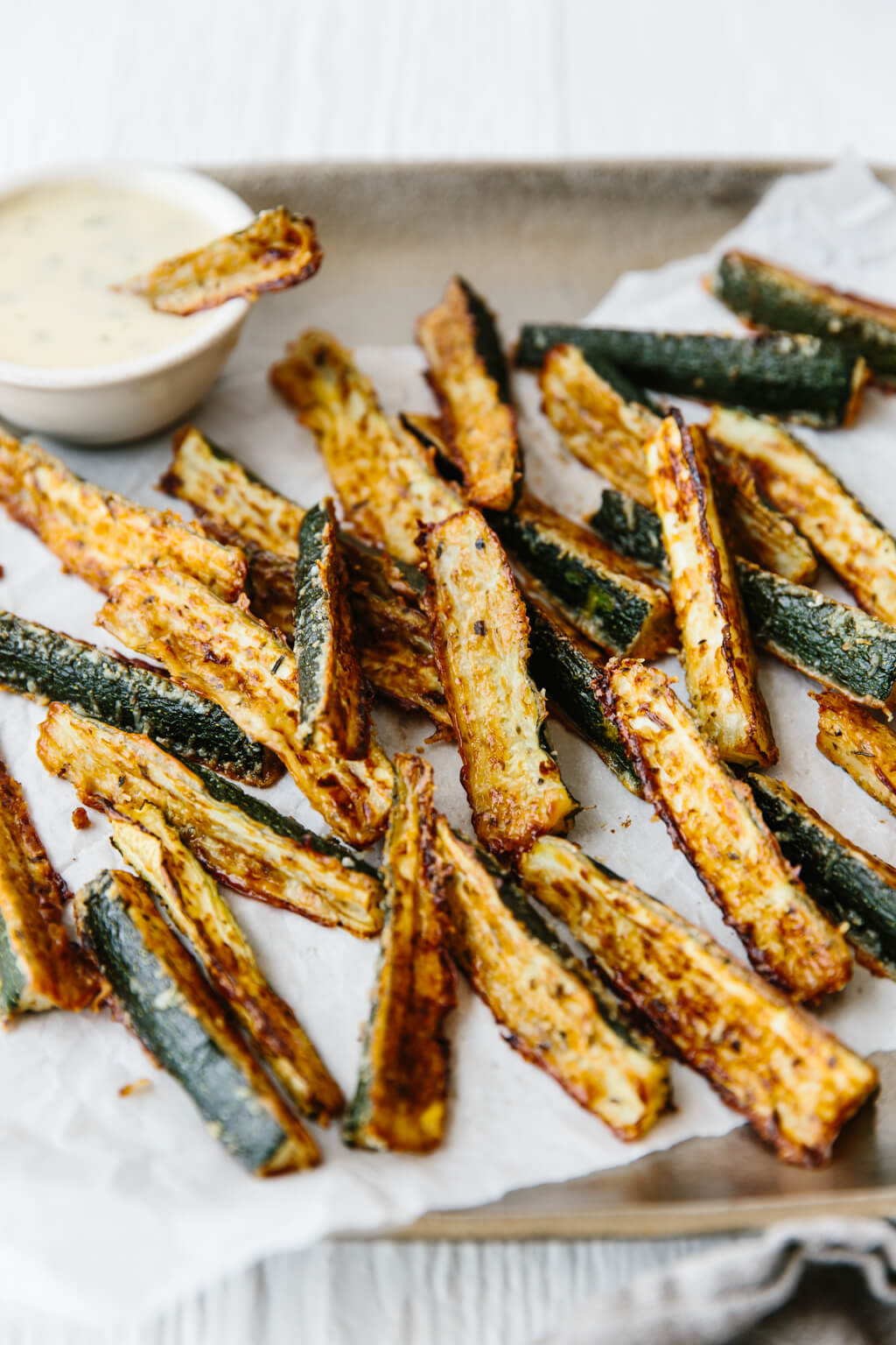 Baked zucchini fries on a platter.