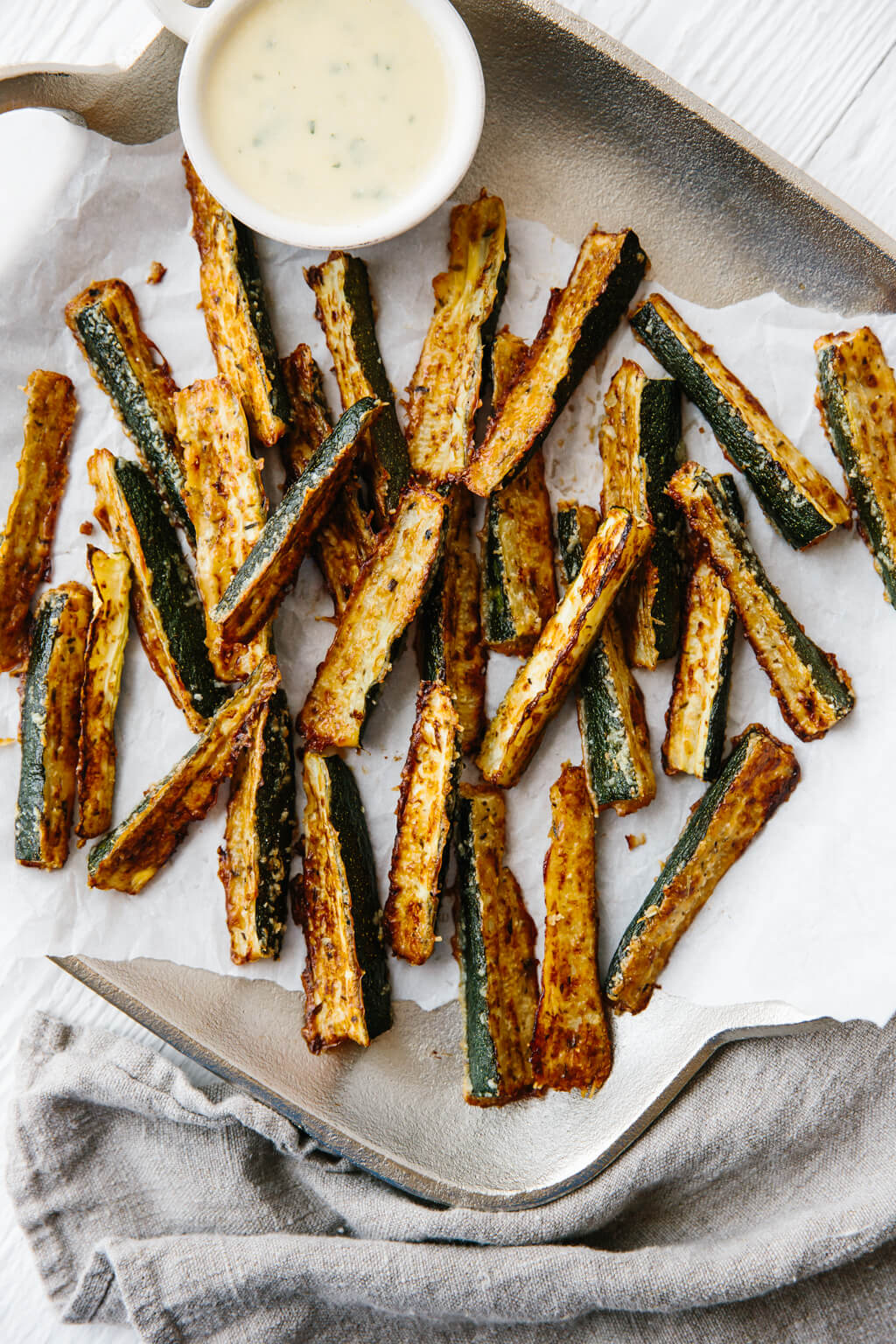 These baked zucchini fries are ultra cheesy and flavorful with freshly grated Parmesan cheese. They're also gluten-free, low-carb, paleo and keto-friendly for a delicious, healthy snack recipe.