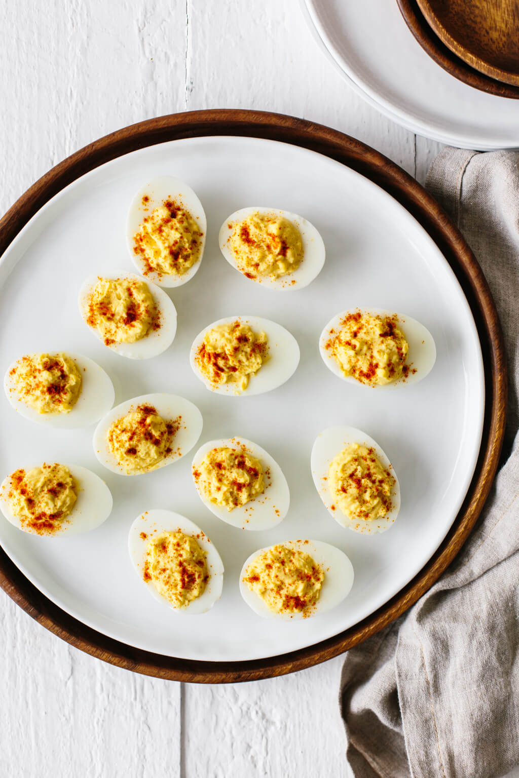 One dozen deviled eggs on a white plate.