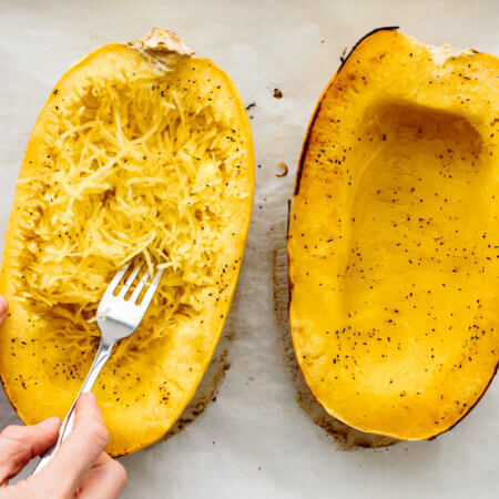 Scraping the inside of the spaghetti squash with a fork.