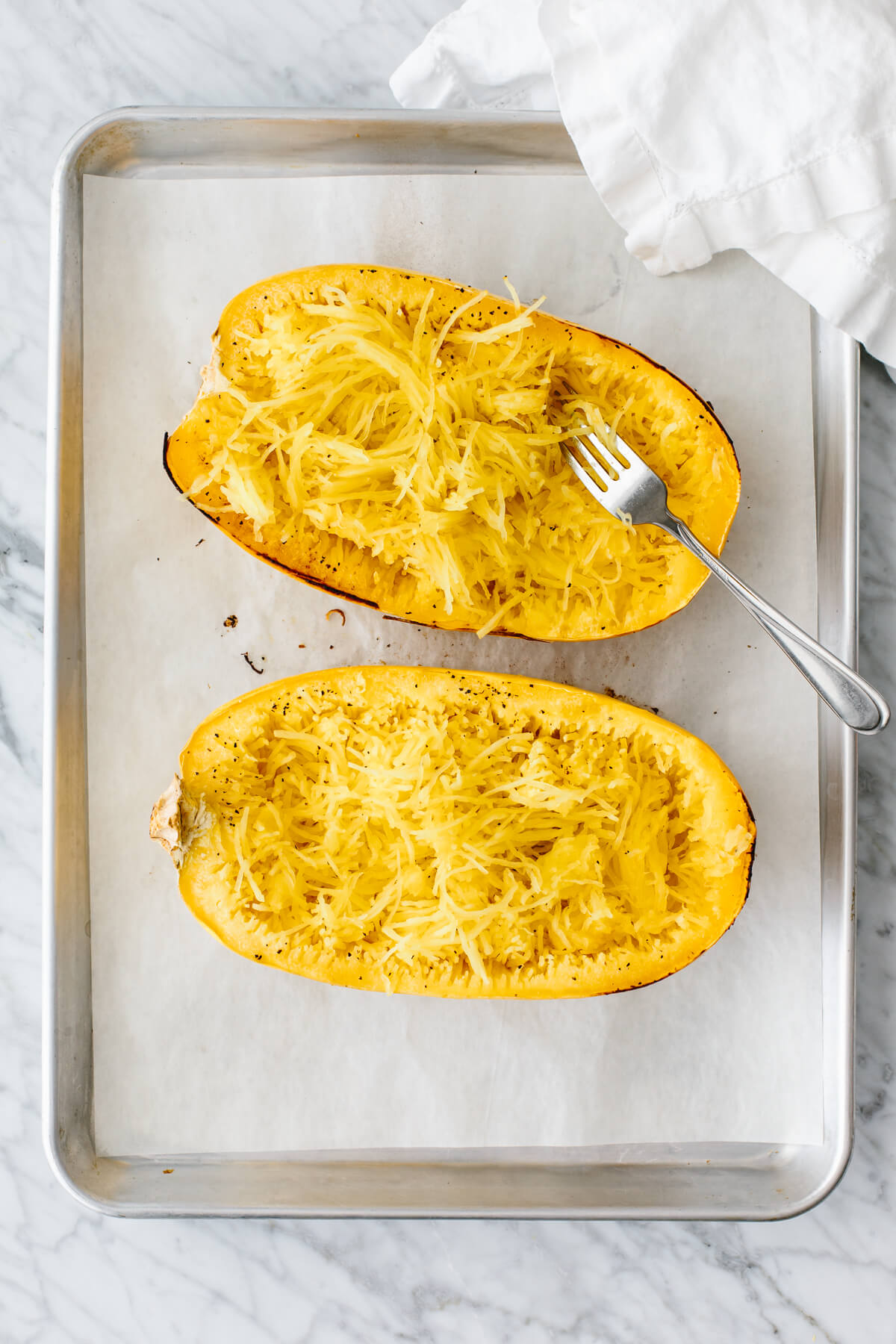 Two spaghetti squash halves with strands fluffed up with a fork.