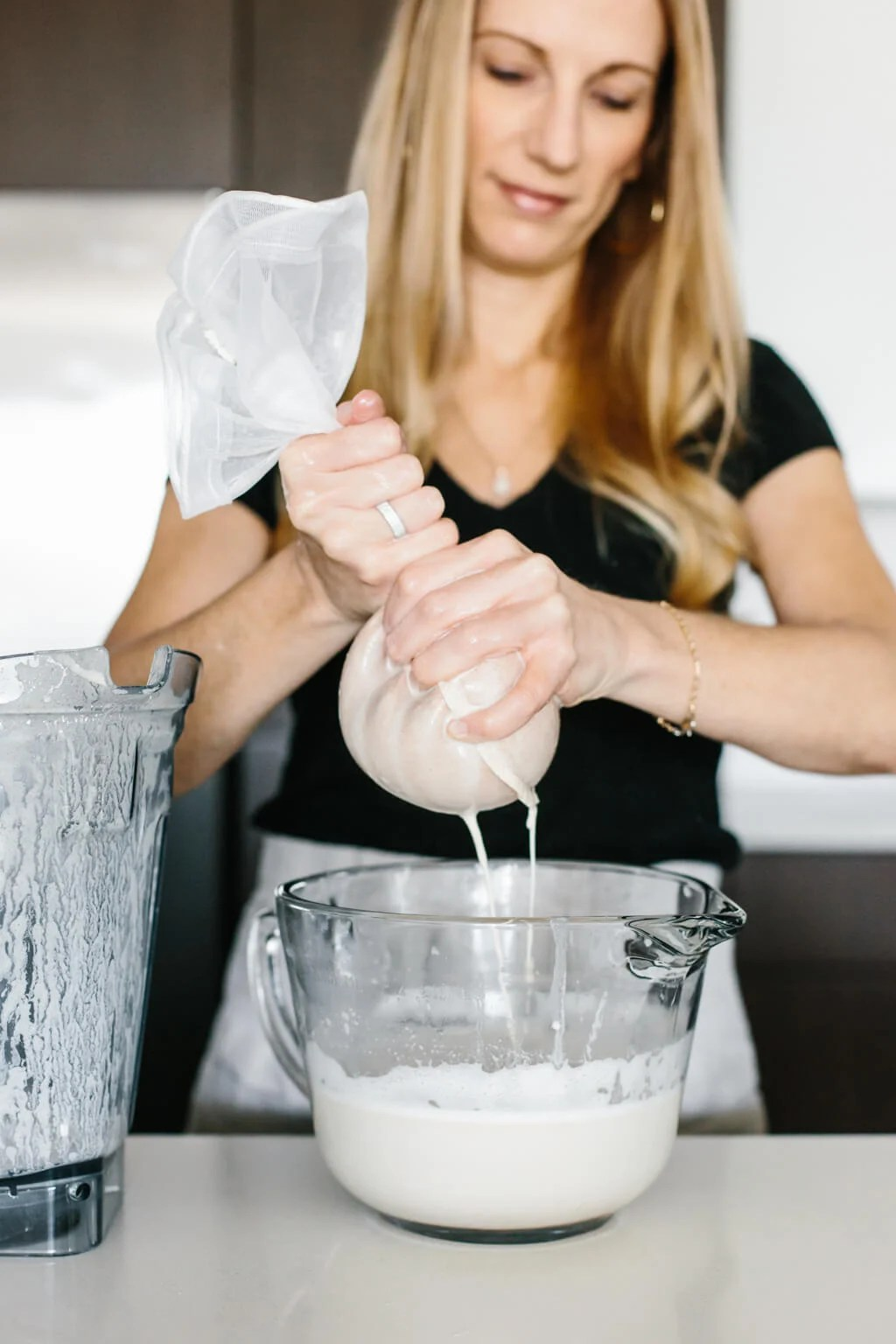 Using hands to squeeze the almond milk in a nut milk bag.