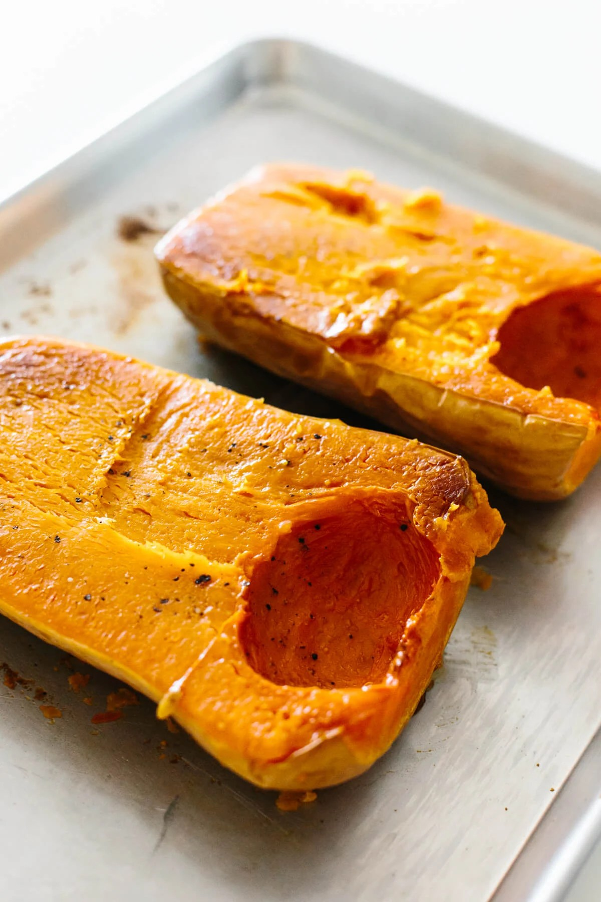 Roasted butternut squash halves on a baking sheet.