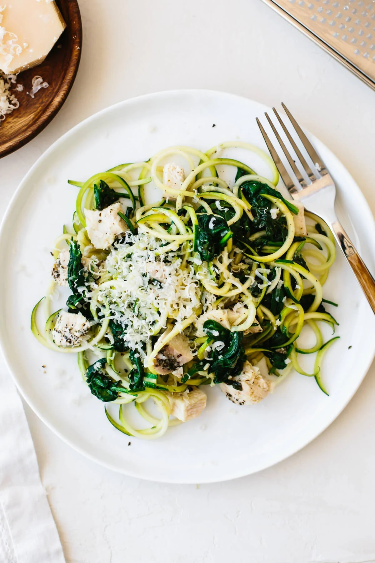 A plate of zucchini noodles with chunks of chicken, sauteed spinach and a sprinkle of parmesan.