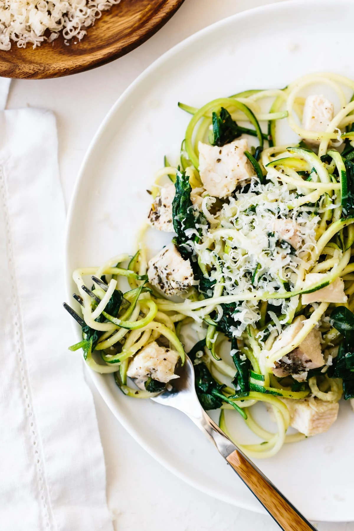 Zucchini noodles with chicken twirled on a fork on a plate.