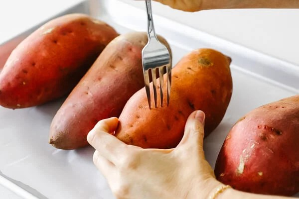 Poking the sweet potato with a fork.