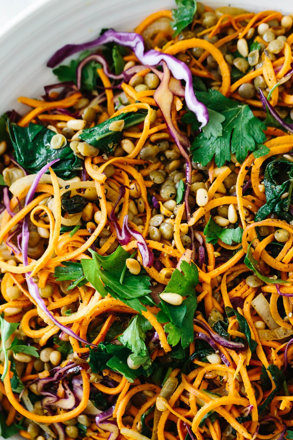 Sweet potato noodles salad is a combination of spiralized sweet potato noodles, cabbage, lentils, sautéed onions and Swiss chard. It's topped off with fresh herbs, toasted pine nuts and a zesty Dijon vinaigrette.