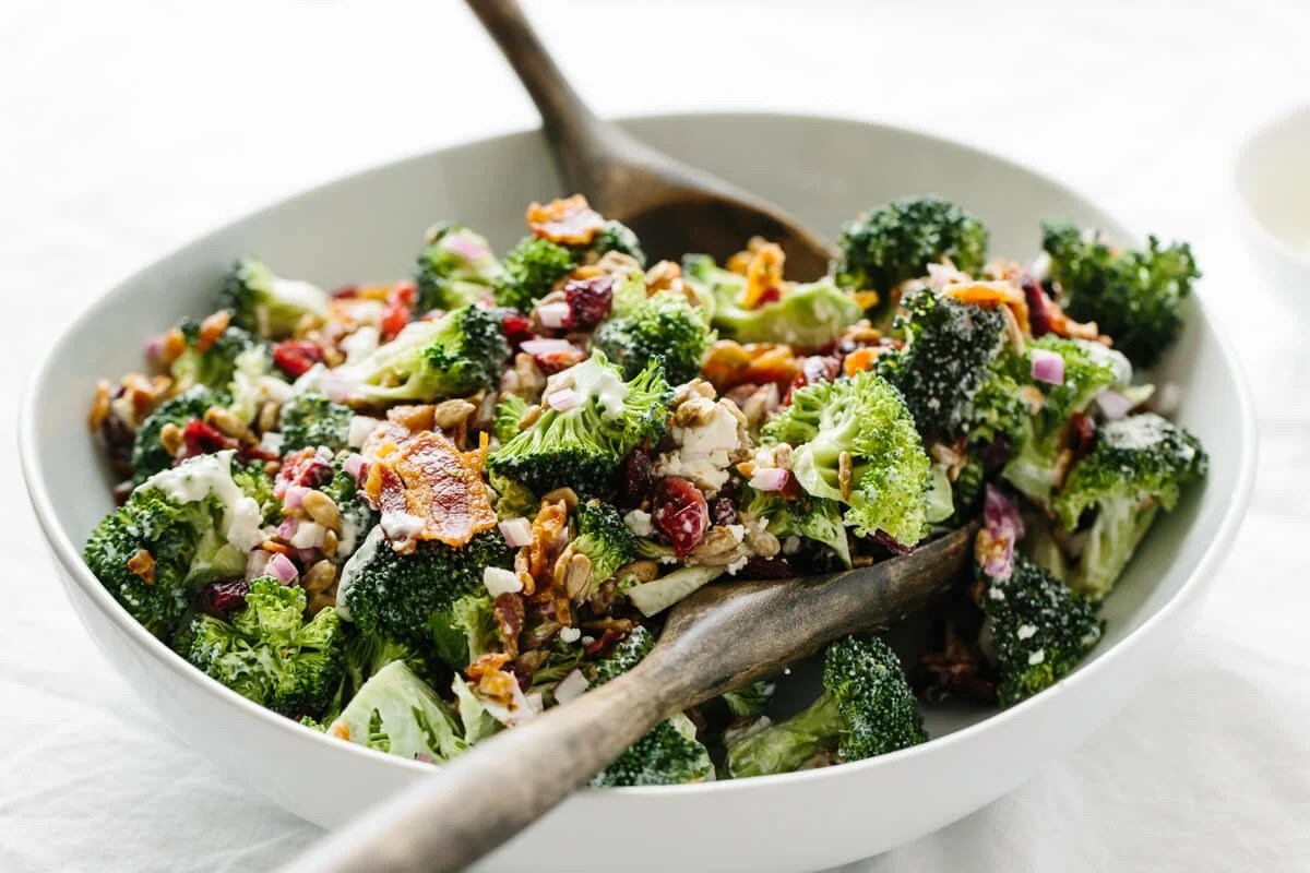 Broccoli salad recipe in a bowl with salad tongs.