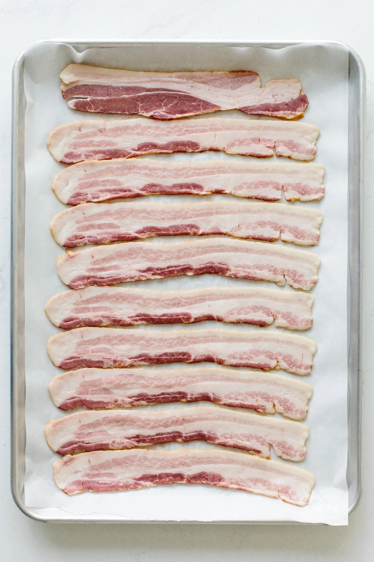 Raw bacon on a sheet tray.