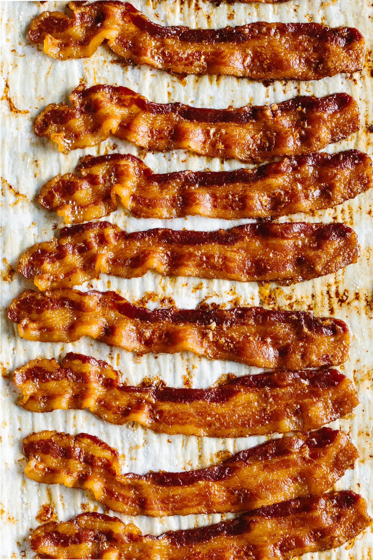 Slices of cooked bacon on a sheet tray.
