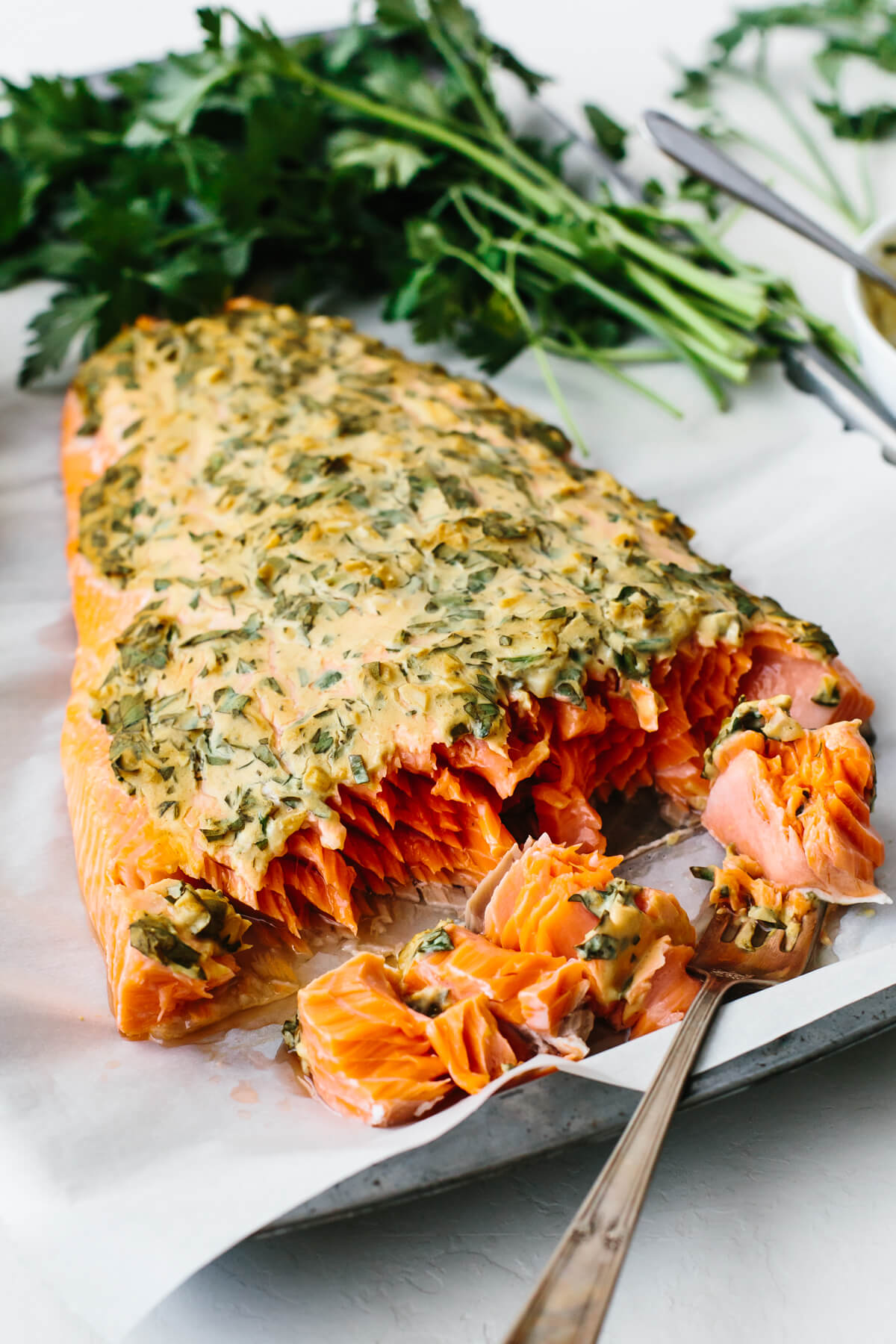A piece of dijon baked salmon next to parsley.