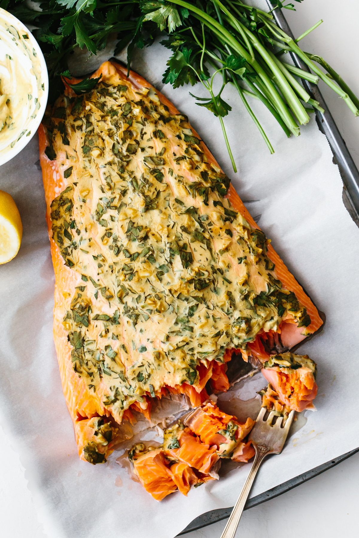 Dijon baked salmon on a tray with a fork.