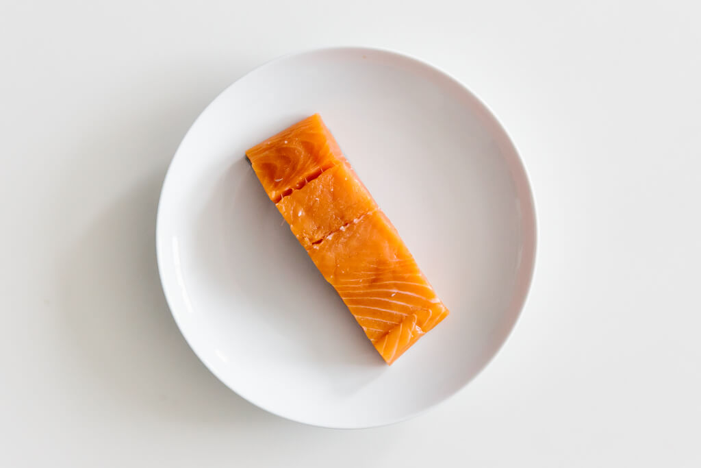 Plate of salmon on a white table.