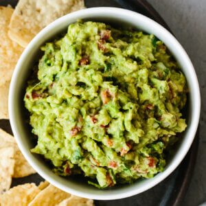 Guacamole recipe in a bowl next to tortilla chips.