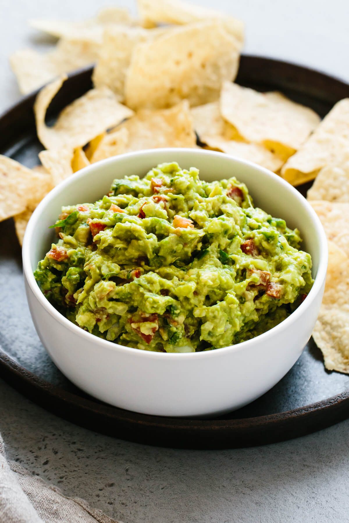 Guacamole in a white bowl surrounded by chips.